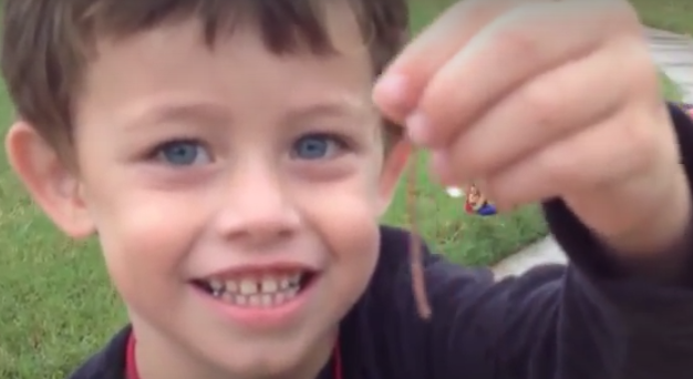 Boy smiling and holding up a wiggly worm