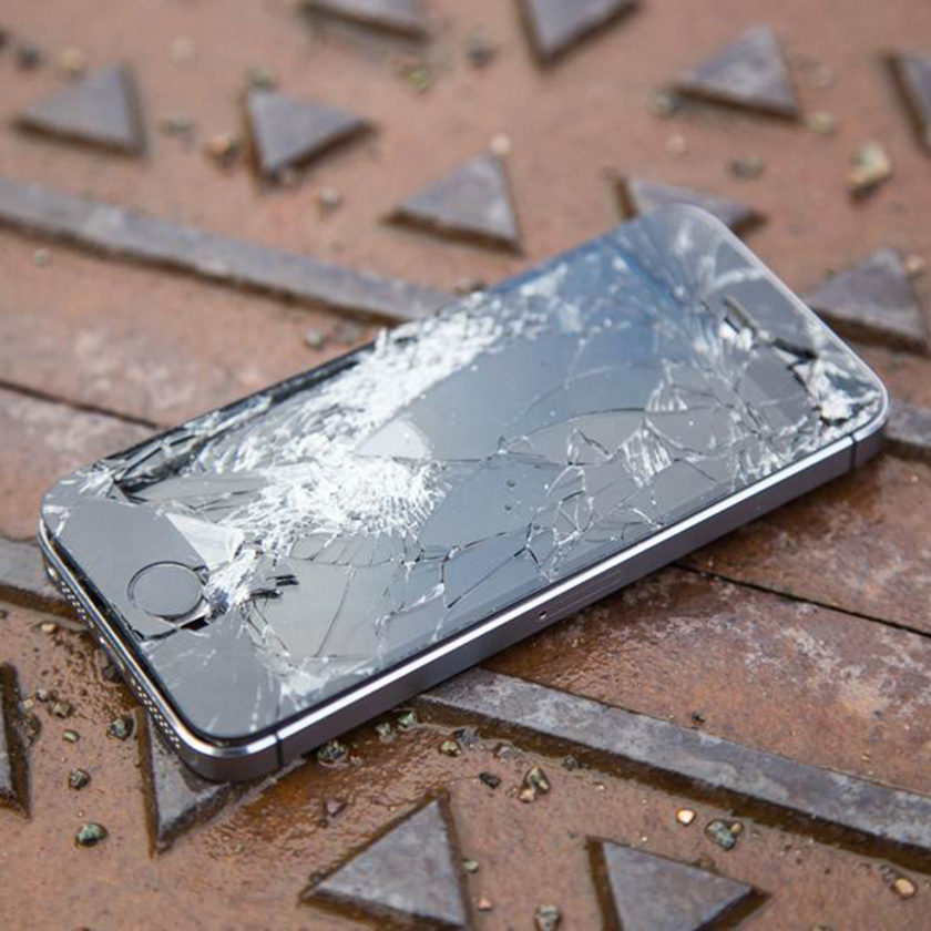 A smashed cellphone on a manhole cover