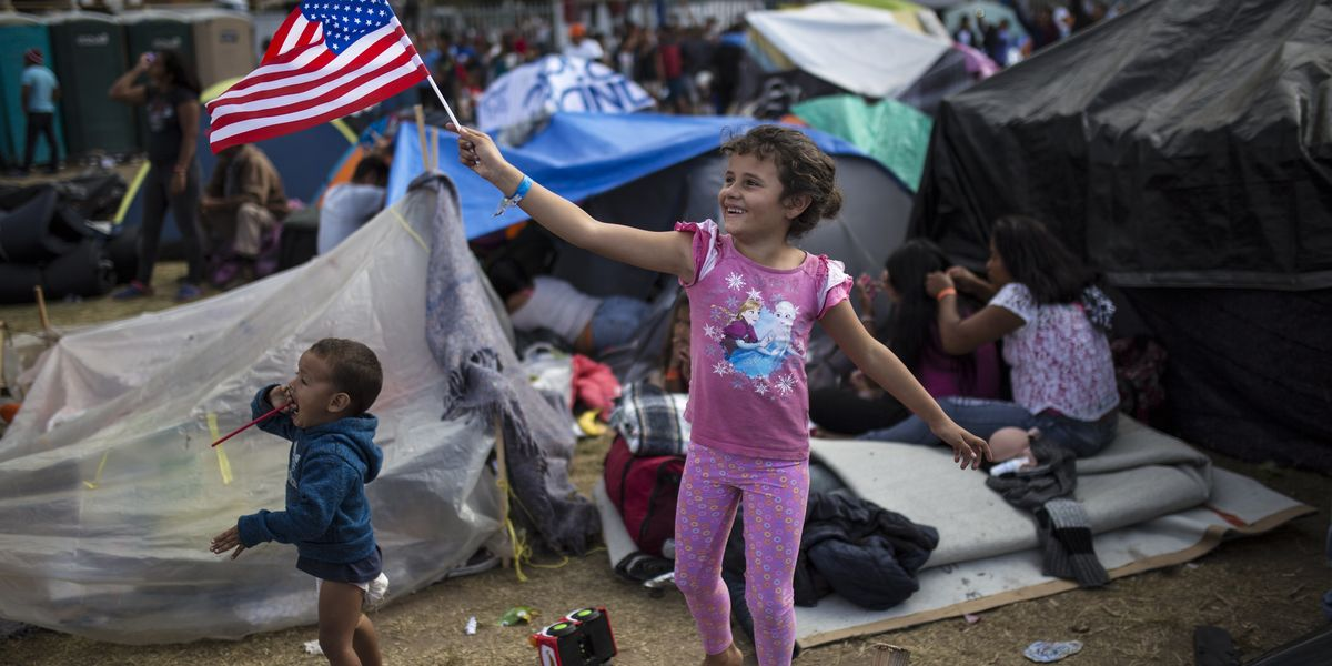 Migrant children smiling, playing and waving an American Flag
