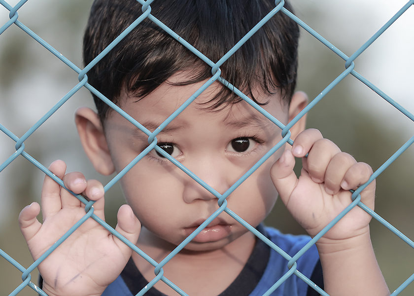 Small boy peering through a chain link fence, looking scared and sad.
