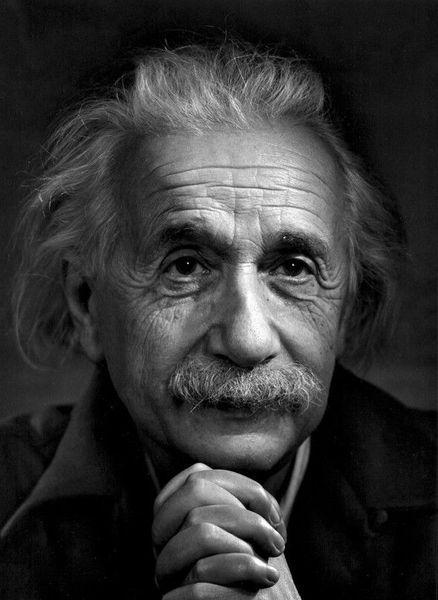A portrait of Albert Einstein, with hands clasped